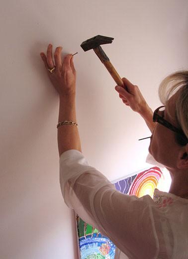Stock Photo: 1606-39189 IN*Portrait femme blonde de profil, lunettes, plantant un clou dans mur, pointe dans la bouche, tableau