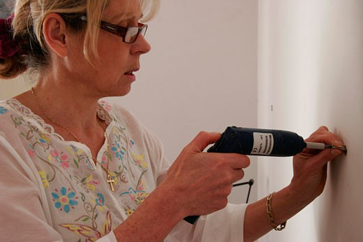 IN*Portrait femme blonde de profil, lunettes, perçant un trou dans mur , cheville, perceuse électrique : Stock Photo