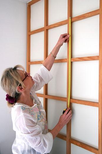 IN*Portrait femme blonde, lunettes, mesurant encadrement en bois sur cloison blanche : Stock Photo
