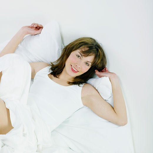 Elevated view on smiling woman posing, lying down on a bed : Stock Photo