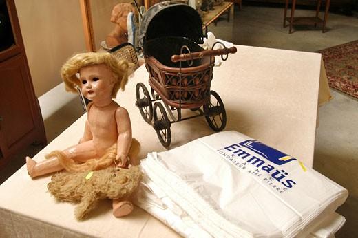 """IN*44. Nantes, salle des ventes de Emmaus, bibelots sur une table (poupée, petit landau, peluche), sacs """"Emmaüs"""" : Stock Photo"""