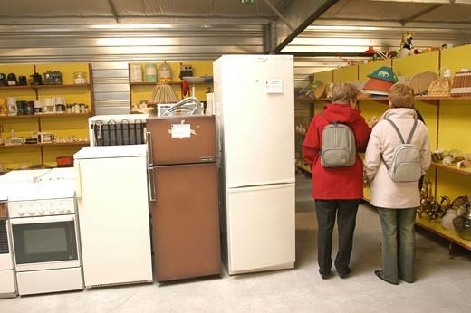IN*44. Nantes, salle des ventes de Emmaüs, produits électro-ménagers d'occasion, 2 femmes de dos : Stock Photo