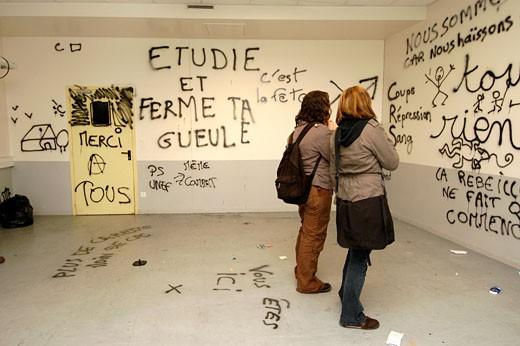IN*44. Nantes, dégradation des locaux de la faculté de sociologie suite à leur occupation par des étudiants en lutte contre le CPE (contrat première embauche), tags et slogans sur les murs, 2 étudiantes de dos (04/2006) : Stock Photo