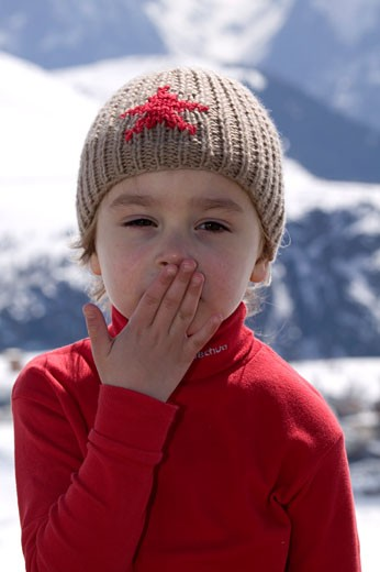 Portrait little girl posing, hand on her mouth, bonnet, blue sweat, mountains in the background : Stock Photo