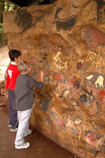 France, Midi-Pyrénées, Ariège,Tarascon sur Ariège, Prehistoric Park, 2 little boys painting on rock : Stock Photo