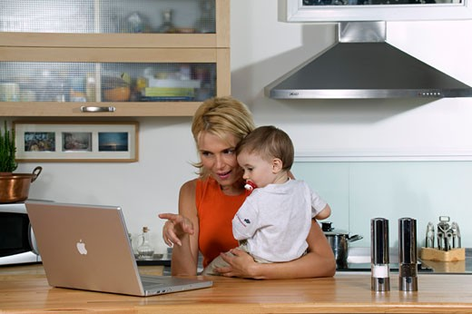 Svetlana in the kitchen, showing computer screen to Anthony : Stock Photo