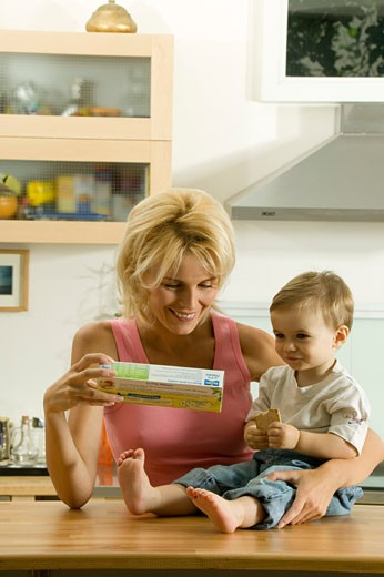 Woman looking at pack of cakes and holding Anthony : Stock Photo