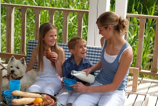 Three children at breakfast, outdoors : Stock Photo