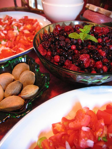 Close-up of tomato salad, red berries and almonds : Stock Photo