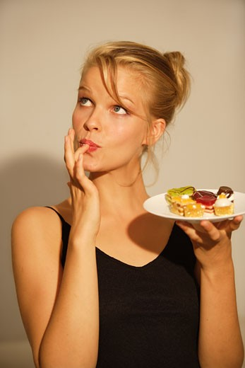 Portrait of a young girl eating petit four : Stock Photo
