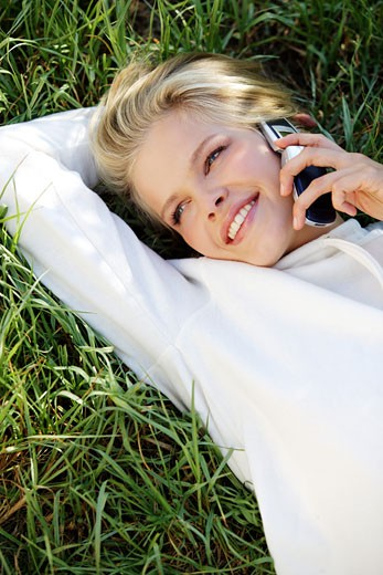Christina smiling, lying in the grass, on the phone : Stock Photo