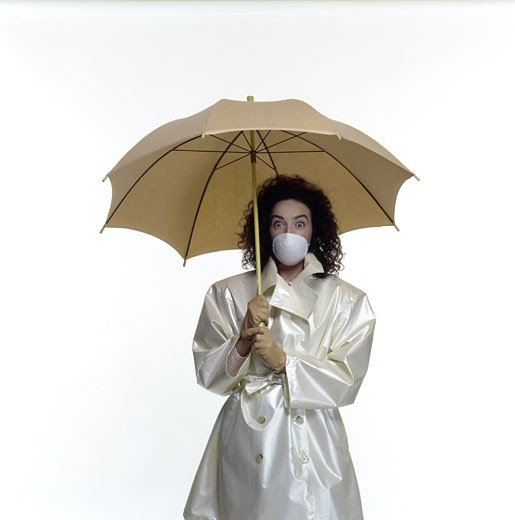Woman with raincoat, umbrella, gloves and mask agains her mouth, studio : Stock Photo