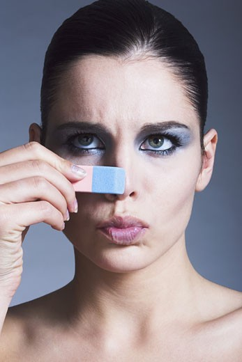 Portrait of a young woman touching her nose with eraser : Stock Photo