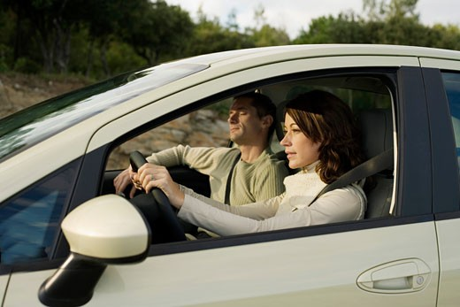 Couple in a car, woman driving, man sleeping : Stock Photo