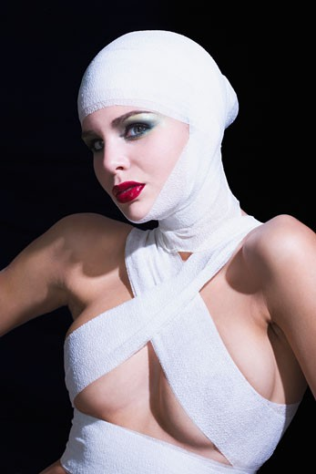 Naked woman with bandages on head and breast, shrugging : Stock Photo