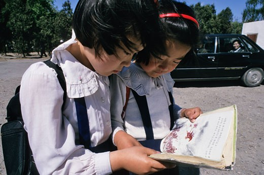 North Korea, Pyongyang,  young scholl girs reading the story of Cheollima (a legendary horse who was very fast) : Stock Photo