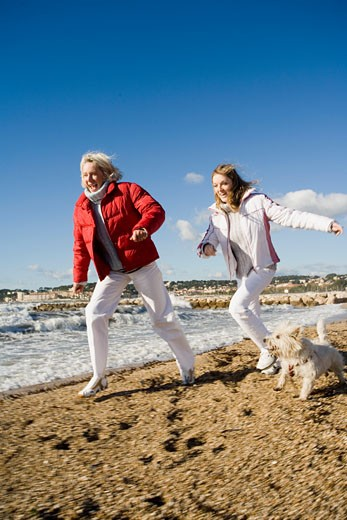 Matureand young women on a beach : Stock Photo