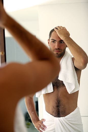 Man looking in the mirror, stripped to the waist : Stock Photo