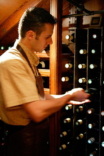 France, wine cellar, wine waiter choosing a bottle : Stock Photo
