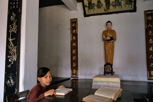 Stock Photo: 1606-50098 Vietnam, Hue, young monk studying holy buddhist books at the Bao Quoc temple