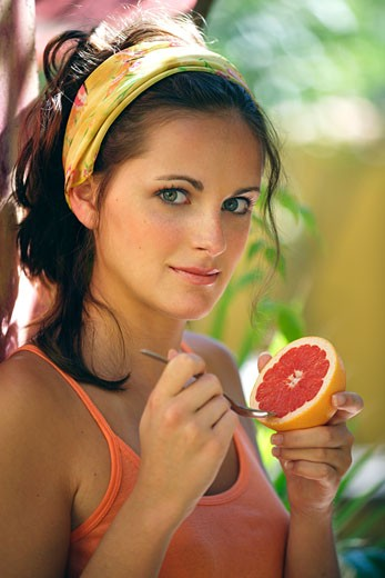 Portrait of woman eating grapefruit : Stock Photo