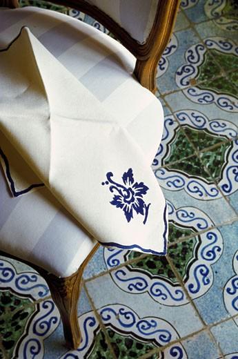 Serviette brodée sur une chaise dans une salle a manger au carrelage ancien : Stock Photo