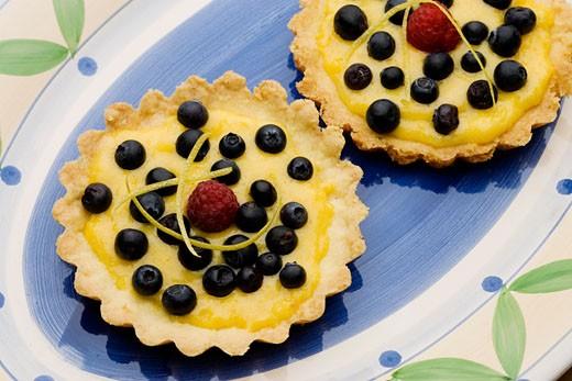 Lemon tarts with whortleberries : Stock Photo