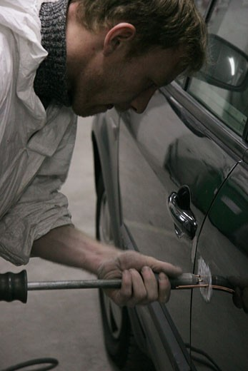 Stock Photo: 1606-55240 Garage interior, man working on a car