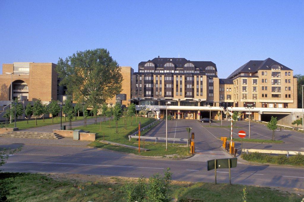 Belgique, Louvain-la-Neuve, parking vide devant immeuble, route au premier plan : Stock Photo