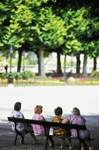 France, Montpellier, four old women sitting on a bank, in a park : Stock Photo