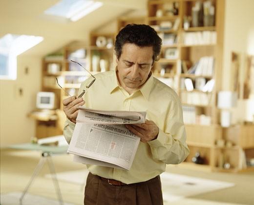 :Georges, lunettes à la main, chemise jaune, debout dans bureau, regardant article dans journal, bibliothèque au fond : Stock Photo