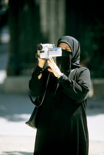 Woman wearing a veil using a camcorder : Stock Photo