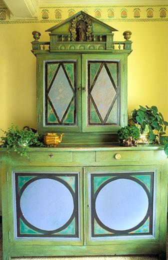 Sud-Ouest, intérieur, gros plan sur buffet ancien restauré, peint en vert, mur jaune + frise : Stock Photo