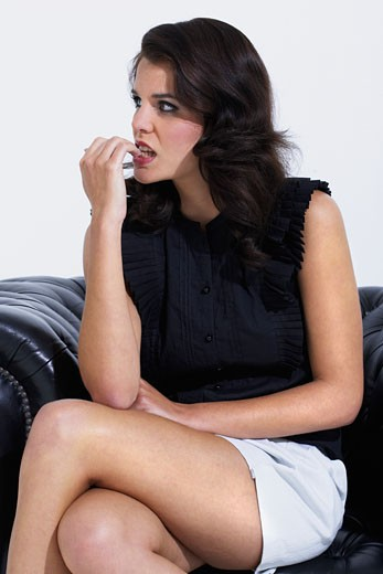 Woman sitting cross legged, biting her nails : Stock Photo