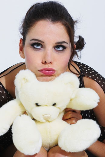 Woman hugging a teddy bear, making a face : Stock Photo