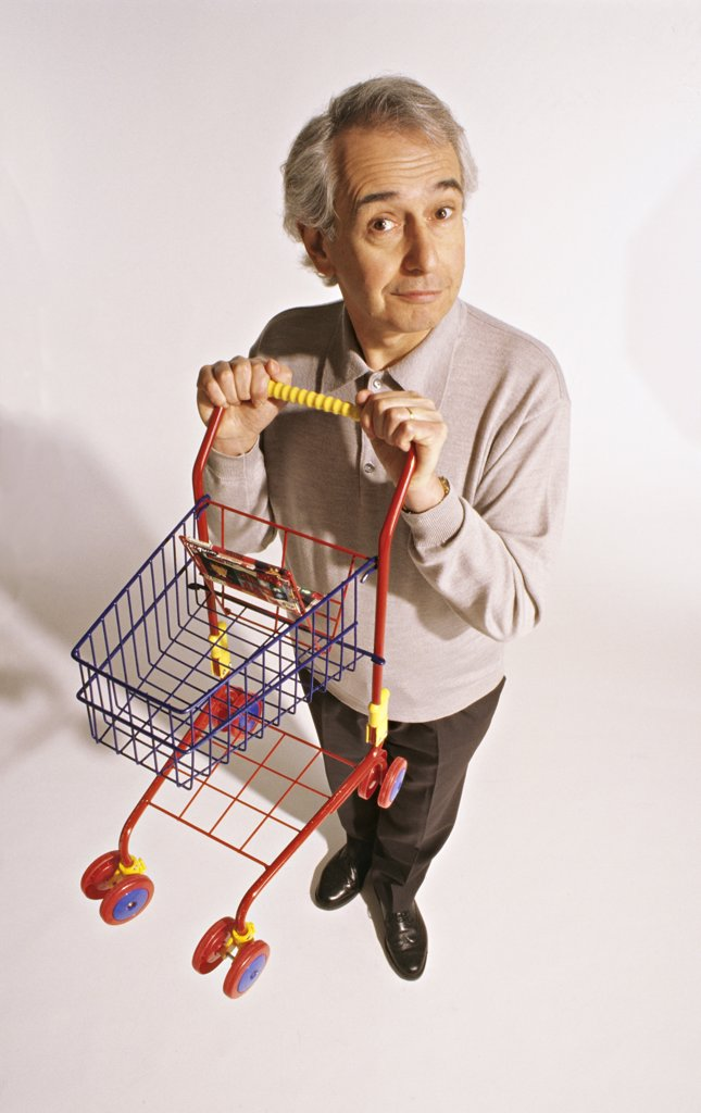 Stock Photo: 1606-71249 Senior man holding a little shopping-trolley, studio