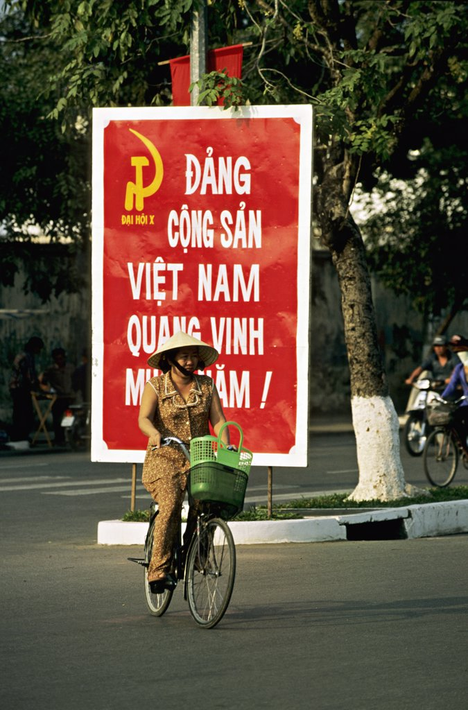 Stock Photo: 1606-71465 Vietnam, Mekong delta, Can Tho, cyclist and poster of communist party