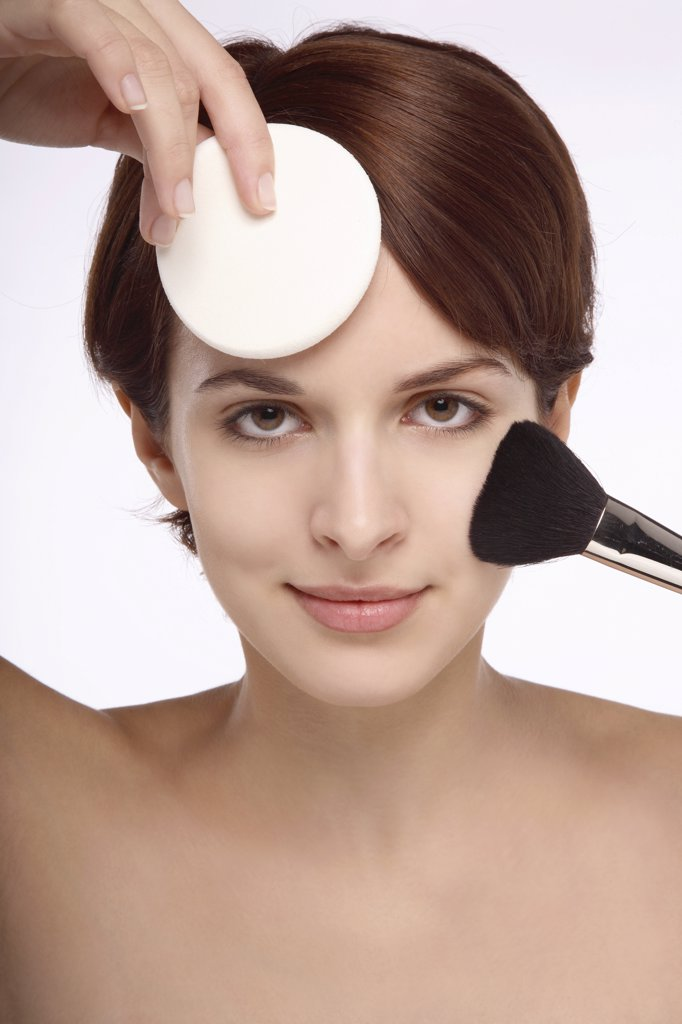 Stock Photo: 1606-74845 Portrait of a young brunette woman brush and sponge on face