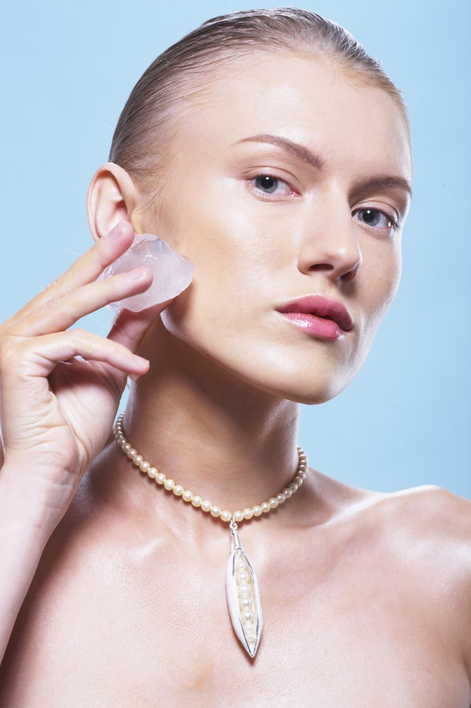 Portrait of a young woman with an ice-cube on her cheek : Stock Photo