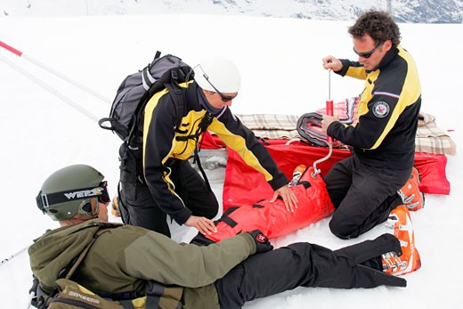 France, Alps, Savoie, Méribel, ski patrol members helping skier : Stock Photo