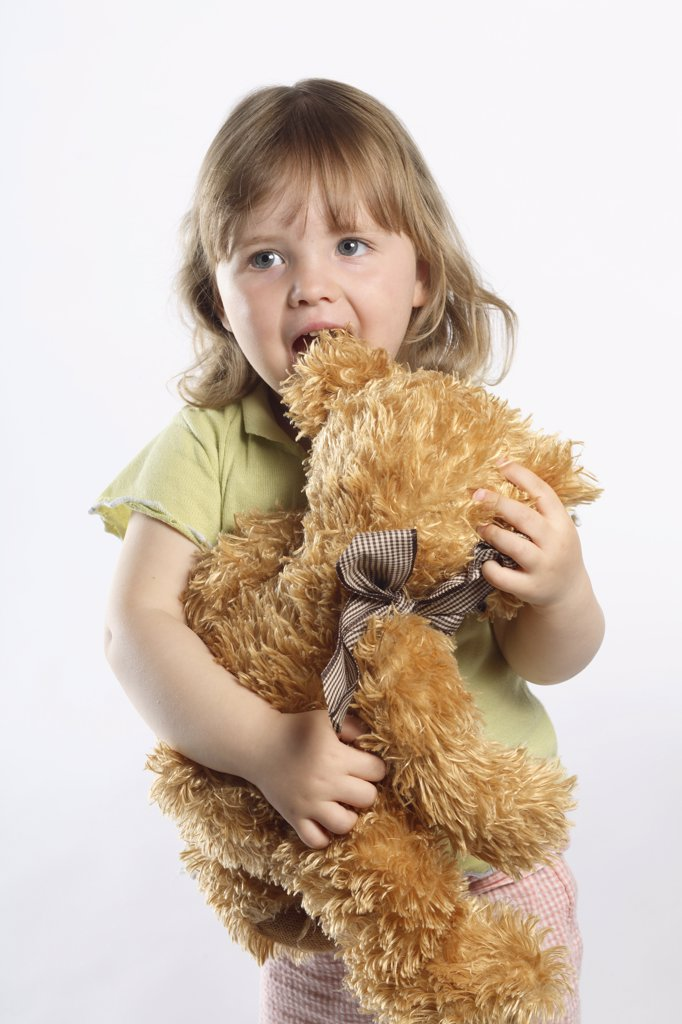Stock Photo: 1606-77703 Little girl holding a stuffed animal, studio