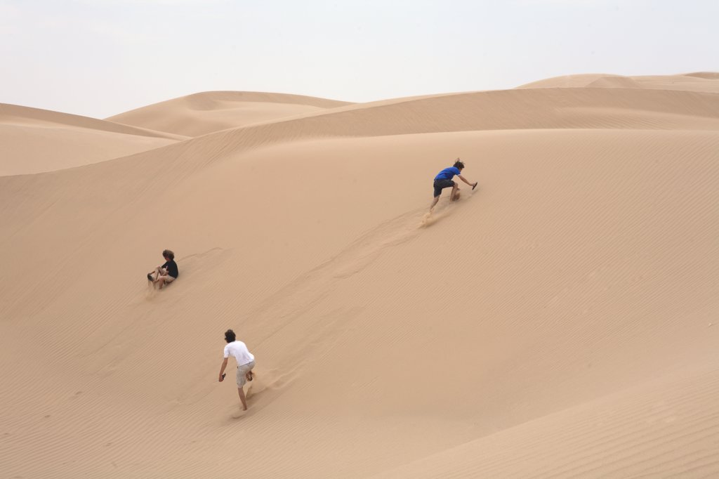 US, California, three boys on dune near Barstow : Stock Photo