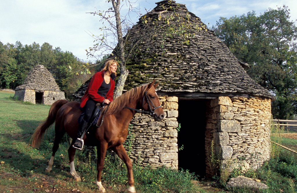 France, Aquitaine, Dordogne, horse rider and dry stone huts : Stock Photo