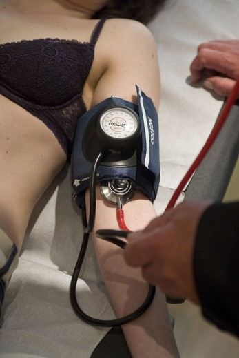 Doctor taking blood pressure of a patient : Stock Photo