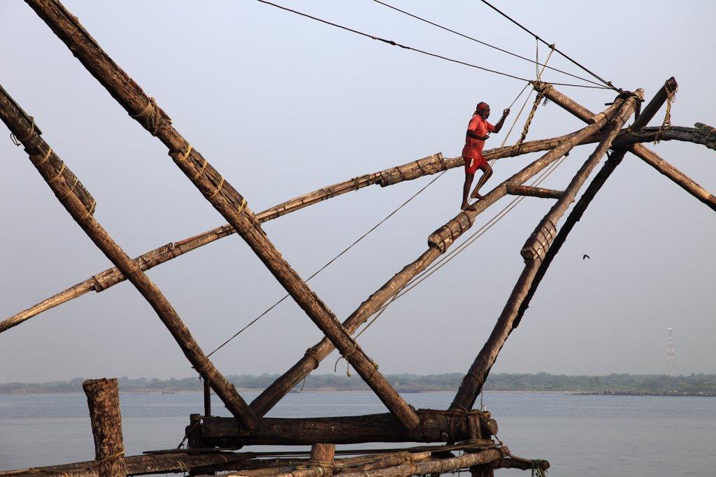 India, Kerala, Kochi, Fort Cochin, man working on chinese fishing nets : Stock Photo