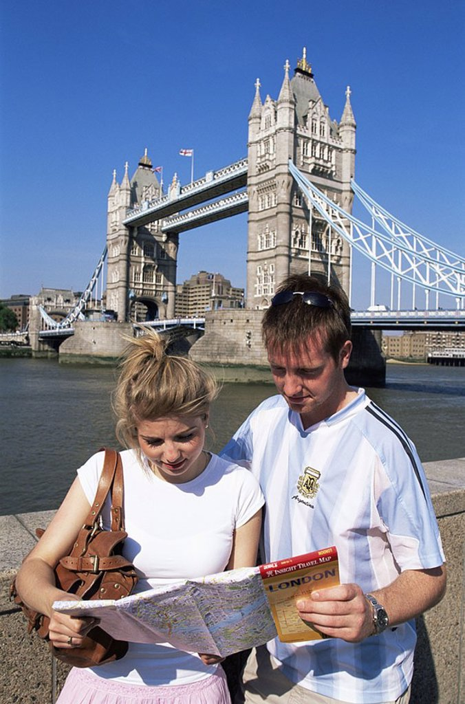 Stock Photo: 1609-21700 England,London,Young Tourist Couple looking at London Map in front of Tower Bridge