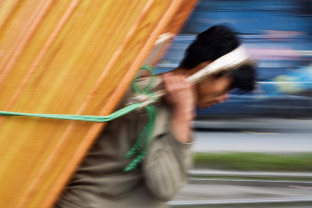 India, West Bengal, Darjeeling, Porter carrying load on back : Stock Photo