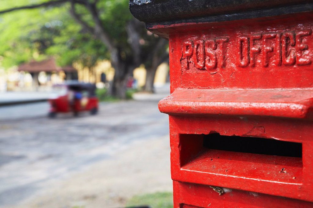 Red post box with tuk tuk in background, Galle, Sri Lanka : Stock Photo