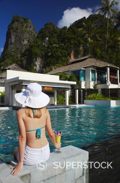 Woman relaxing by pool with drink in Bhu Nga Thani Resort and Spa, Railay, Krabi Province, Thailand MR : Stock Photo