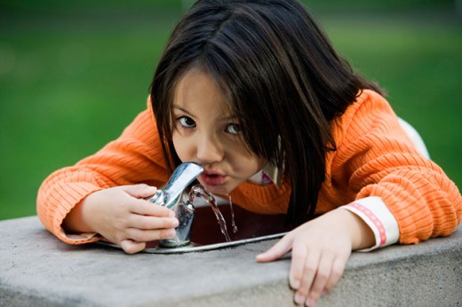 Stock Photo: 1610-184 Portrait of a girl drinking water from a water fountain